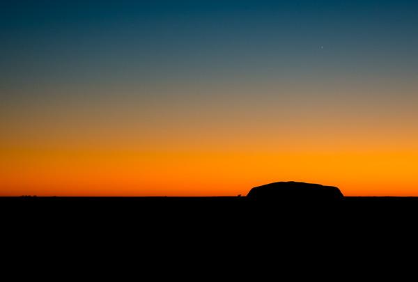Uluru in silhouette at sunrise.