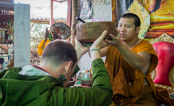 Receiving a blessing and making an offering to the Ajarn.