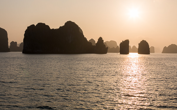 Sunset in Halong Bay, with the limestone karsts in the foreground.