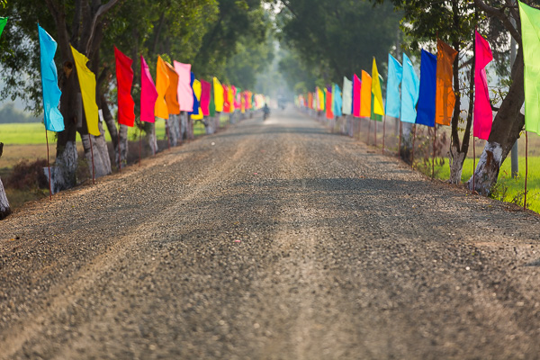 Lush greenery and blue skies are typically complemented by colorful clothing, buildings, and places of worship. These flags were lining the road to a new temple outside Kampong Chhnang, Cambodia.